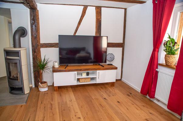 Smart TV neben dem gemütlichen Kaminofen. Für das Sideboard wurden originale Eichenbalken aus dem Haus verarbeitet.