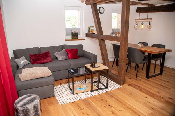 Wohnzimmer mit Sitzecke und Esstisch. Der Esstisch wurde aus alten Eichenbalken in der eigenen Tischlerei gefertigt.