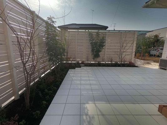 ホワイトのタイルテラスと木調樹脂フェンス
