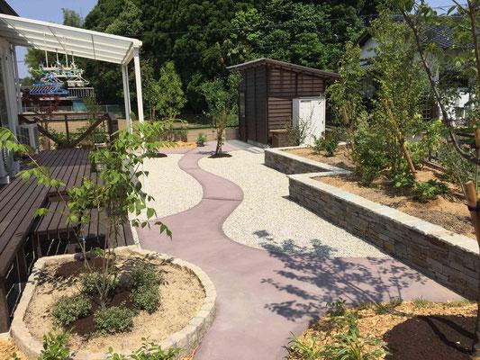 自然石の小端積花壇の直線とカラーの散策路の曲線のバランス