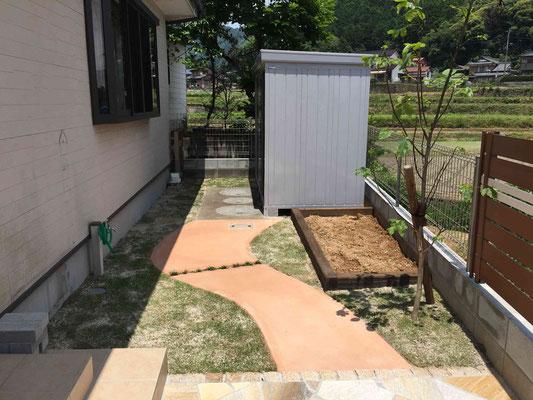オレンジのカラー園路と物置と菜園