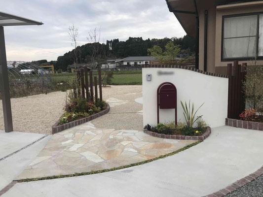 白の無理壁仕上げの門塀と印象的な赤(ボルドー)のポスト ボビ