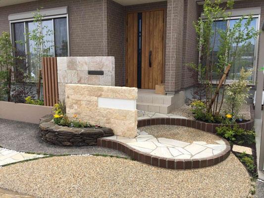 自然石の石張り門塀とレンガの曲線ステップ
