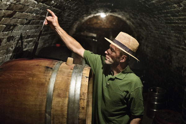 ralf wassmann is taking wine out of a barrel
