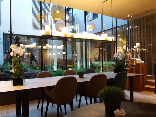 Vue du restaurant sur le patio où se cotoient lanternes, art et végétaux.
