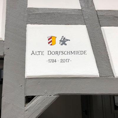 Handgemalter Hausnamen auf Hauswand.