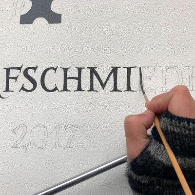 Malen des Hausnamen 'Alte Dorfschmiede' auf die Wand.