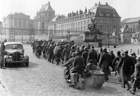 Una columna de prisioneros de guerra franceses bajo vigilancia nazi alemana fuera del Palacio de Versalles, 1940. WWII Pictures
