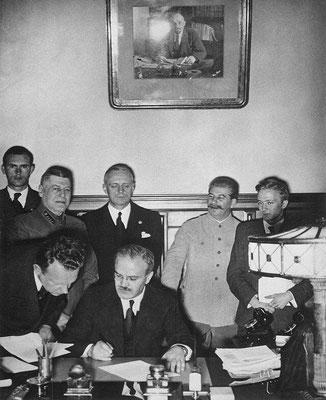 Viacheslav Mólotov está a punto de firmar. Tras él se encuentran Joachim von Ribbentrop (con los ojos cerrados) y a la derecha de este, en la foto, Iósif Stalin (sonriente y apoyado contra la pared). En el cuadro que hay arriba, una fotografía de Lenin.