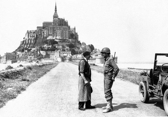 Un hombre francés habla con un soldado estadounidense frente al Monte Saint-Michel, Francia 1944. WWII Pictures