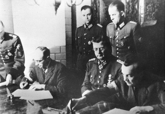 """Firma de la """"Capitulación de Varsovia"""" en Ożarów Mazowiecki. Desde la izqda: Coronel polaco Kazimierz Iranek-Osmecki, SS-Obergrupenführer Erich von dem Bach-Zelewski y Teniente Coronel polaco Zygmunt Dobrowolski."""