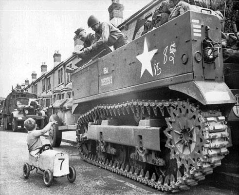 Un niño británico saludando a los soldados estadounidenses de un tanque M5, mientras estos se reúnen en el sur de Inglaterra para el desembarco de Normandía, primavera de 1944. WWII Pictures