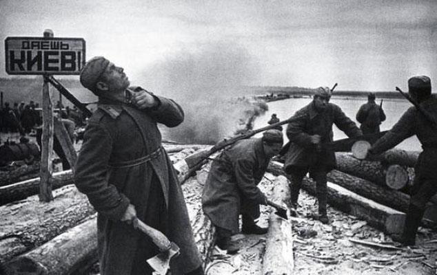 """Soldados rusos soviéticos construyendo balsas para cruzar el río Dniéper, en el letrero: """"¡A Kiev!"""""""