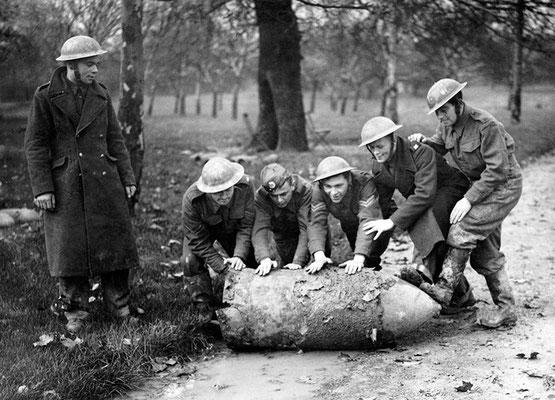 Miembros de una brigada de eliminación de bombas rodando una bomba nazi alemana sin explotar a través de un parque en Londres, 1940.