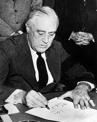 Franklin D. Roosevelt firmando la declaración de guerra contra el Imperio del Japón. Abbie Rowe, National Archives and Records Administration.
