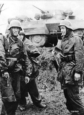 """Soldados nazis alemanes entre vehículos destruidos del 14º Grupo de Caballería de los Estados Unidos en Poteau (Bélgica) con el mismo """"famoso"""" soldado cuya identidad sigue siendo desconocida. Los soldados fuman cigarrillos Lucky Strike."""