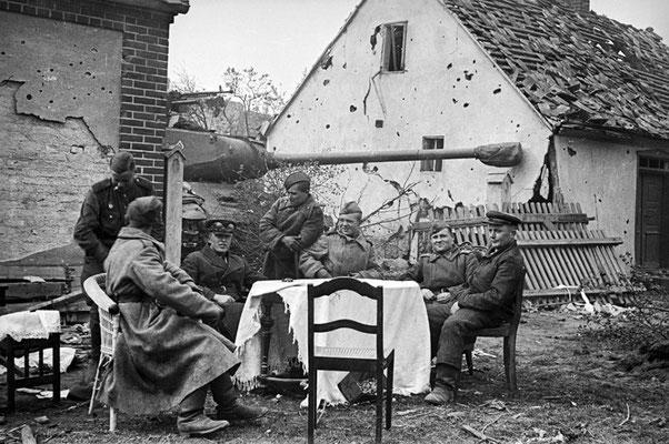 Soldados rusos soviéticos sentados alrededor de una mesa y detrás de ellos un tanque pesado IS-2 en los suburbios de Berlín, 1945. WWII Pictures