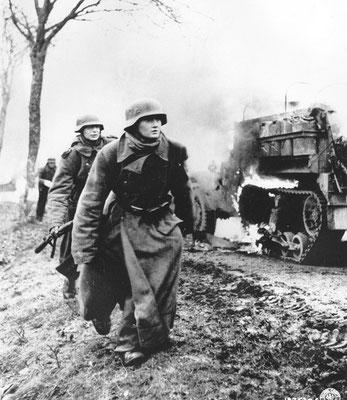 Soldados nazis alemanes entre vehículos destruidos del 14º Grupo de Caballería de los Estados Unidos en Poteau (Bélgica).
