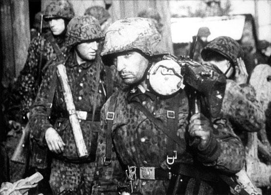 Soldados de las Waffen-SS con uniformes de camuflaje (Erbsenmuster) durante la primera fase de la ofensiva de las Ardenas. El primer soldado lleva una ametralladora MG 42, diciembre de 1944.