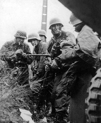 """Soldados nazis alemanes entre vehículos destruidos del 14º Grupo de Caballería de los Estados Unidos en Poteau (Bélgica) con el mismo """"famoso"""" soldado cuya identidad sigue siendo desconocida. Los soldados fuman cigarrillos Lucky Strike. WWII Pictures"""