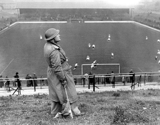 Un observador, mirando hacia los aviones nazis alemanes durante el partido Charlton Athletic vs. Arsenal celebrado en The Valley, Londres 1940. WWII Pictures