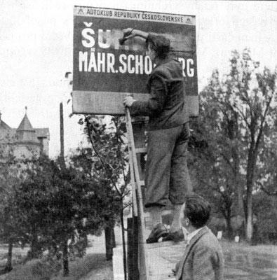 Alemanes de los Sudetes borrando el nombre de la ciudad en el cartel de entrada a Šumperk, oct1938.