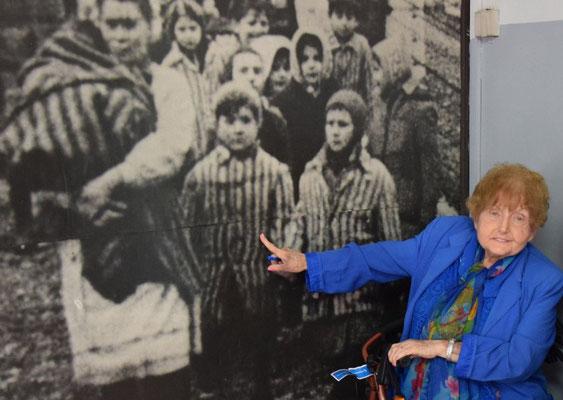Eva Mozes delante de la fotografía de ella y su hermana Miriam en el momento de la liberación que hay en el Museo Memorial Auschwitz-Birkenau.