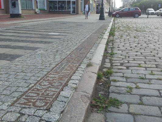 Ahora es el número 22 de la misma calle. Hay unas columnas, dos a cada lado de la calle, que por la noche se iluminan, marcando con luz por donde pasaba el puente que unía las dos partes del gueto de Varsovia. © www.poloniaycentroeuropa.com CC-BY-SA 4.0.