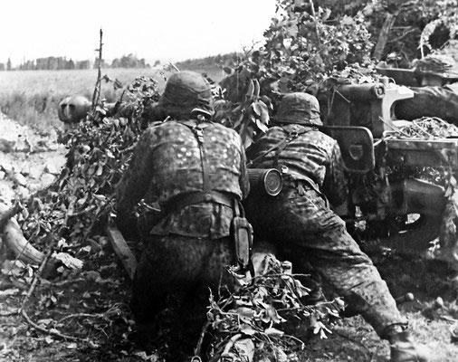 """Artilleros de la 12ª División Panzer SS """"Hitlerjugend"""" cargando un PAK 40 antitanque, camuflado en el terreno, en Normandía 1944. WWII Pictures"""