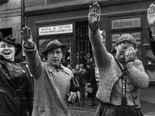 Una mujer llora desconsolada mientras se ve obligada a hacer el saludo nazi a las tropas invasoras. Bundesarchiv Bild 183-H13160, Beim Einmarsch