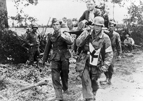 Cuatro soldados nazis alemanes capturados llevan a un compañero herido pasando delante de las tropas estadounidenses, en Normandía 1944. WWII Pictures