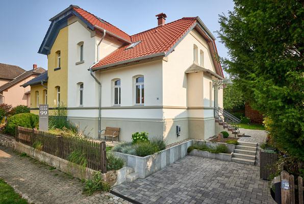 1899 - Ferienhaus, Seminarhaus und Kochwerkstatt / Nordwestansicht von der Straße mit Vorgarten und Pkw-Einstellplatz