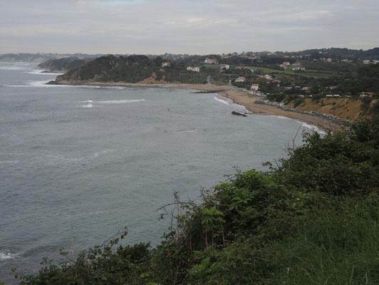 Auf der Steilküste auch unser Wohnwagen, im Wasser (die Punkte) warten wieder die Harten auf die ganz große Welle