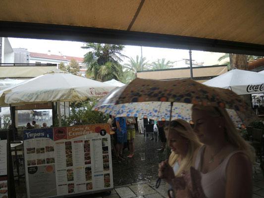 Es regnet und alle fliegenden Händler verkauften plötzlich Regenschirme, statt Gucci-Taschen