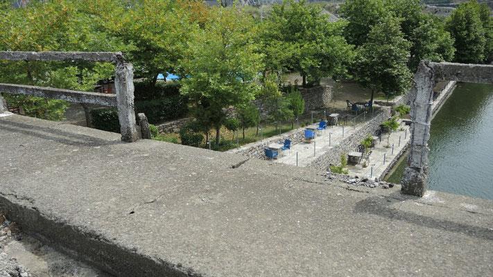 Direkt unter dieser Brücke liegen die Zimmer des Hotels... Im Hintergrund der Campingplatz Koman
