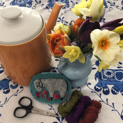 Stitching time! Enjoying tea and flowers while embroidering a felted wool sheep pin brooch