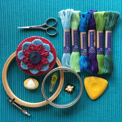 Embroidery supplies - embroidery hoops, floss, scissors, marking chalk and a finished embroidered felt wool flower pin brooch