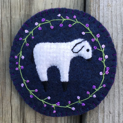 Felted wool sheep on a circle medallion