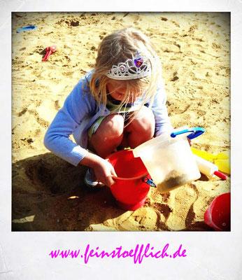 die Prinzessin probiert, ob sie eine Sandskulptur bauen kann