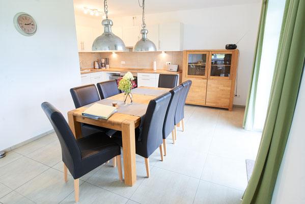 """Blick in die offene Küche mit großem Esstisch der Ferienwohnung """"Am großen Findling"""" auf dem Imkershof der Familie Röhrs in Schneverdingen-Surbostel"""