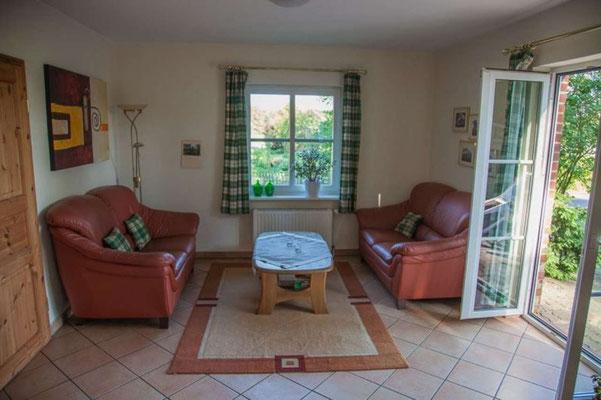 """Wohnbereich mit Zugang zur Terrasse der Ferienwohnung """"Gartenblick"""" auf dem Imkershof der Familie Röhrs in Schneverdingen-Surbostel"""