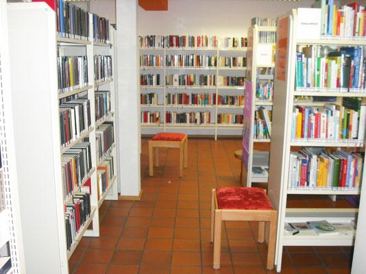 Gang zur Erwachsenenbibliothek im hinteren Bereich der Bibliothek. Auch hier gibt es einen Tisch und Stühle zum längeren Verweilen.