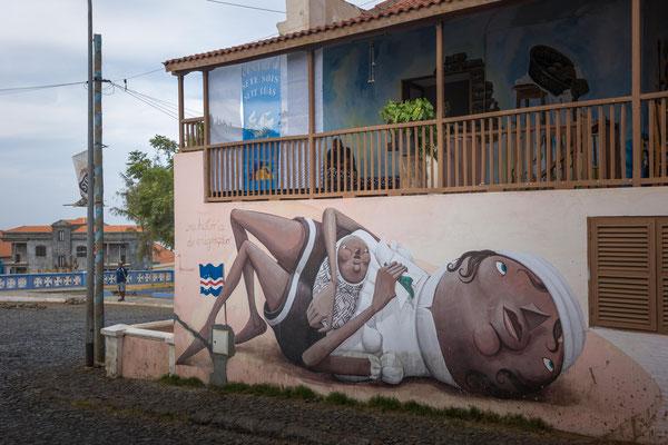Hausmalerei als Symbol gemeint für die Mütter auf den Kap Verden, die oft alleine sind weil die Männer im Ausland arbeiten. (Hohe Arbeitslosigkeit).