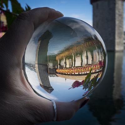 Luzerns Postkartenmotiv - die Kapellbrücke - in der Kugel gedreht und im Wasser der Reus gespiegelt