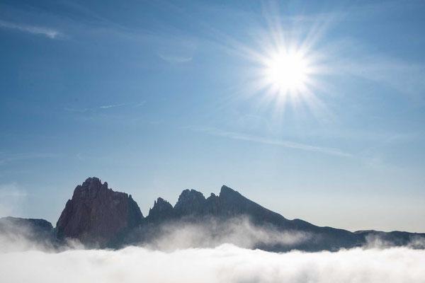 Über den Wolken schauen die Gipfel heraus und die Sonne strahlt