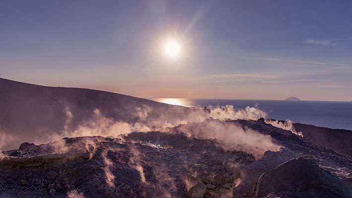 Dampfschwaden steigen in den Himmel während die untergehende Sonne alles in wunderbares Licht taucht. Vulcano, Äolische Inseln, Sizilien