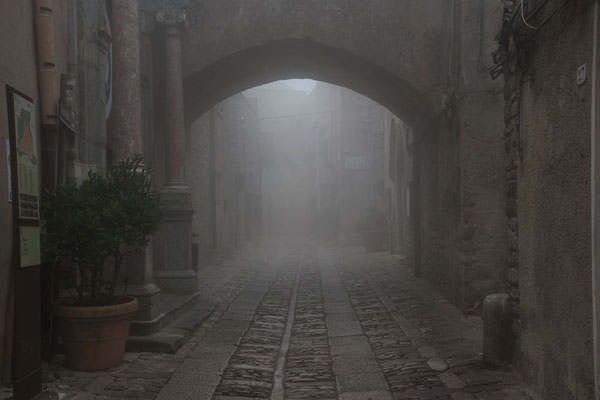 Die Wolken ziehen durch die Gassen und lassen die mittelalterliche Stadt geisterhaft anmuten. Erice, Trapani, Sizilien