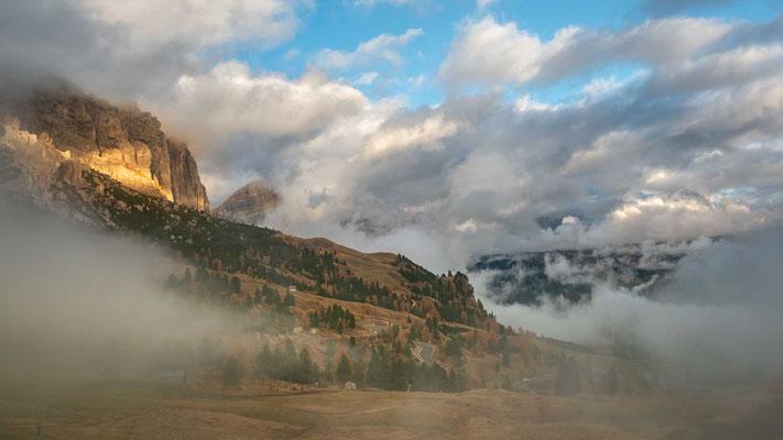 Die letzten Sonnenstrahlen kämpfen sich durch Nebel und Wolken am Grödner Joch