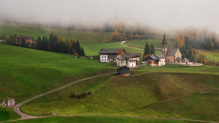 Blick ins Villnöß-Tal, während sich die Gipfel der Geißler Gruppe hinter einer dichten Nebelwand verstecken