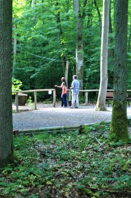 Eine Familie beim Zapfenweitwurf auf dem Walderlebnispfad Sinneswandeln im Gramschatzer Wald